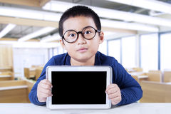 Boy sitting in the class with empty tablet. Portrait of little boy wearing glasses and sitting in the classroom while showing empty tablet screen Royalty Free Stock Photography