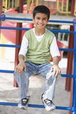 Boy sitting on climbing frame Stock Images