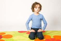 Boy sitting on colorful carpet. Portrait of cute curly boy sitting on colorful carpet Royalty Free Stock Photography