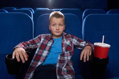 Boy sitting in cinema theatre, watching movie attentively. Boy sitting in comfortable chair in cinema theatre, watching movie attentively. Kid enjoying film or royalty free stock image