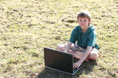 Boy sitting with a computer Royalty Free Stock Image