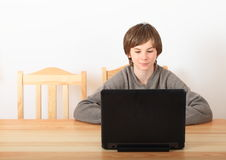 Boy sitting with a computer Royalty Free Stock Photos