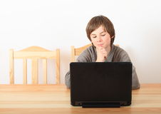 Boy sitting with a computer Royalty Free Stock Images