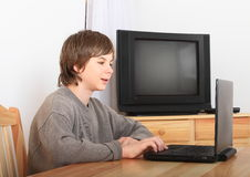 Boy sitting with a computer Stock Photos