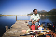 Boy (8-10) sitting on coolbox beside moored motorboat on lake jetty, looking at scenery, smiling Royalty Free Stock Photo