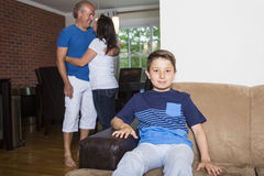 Boy sitting in couch at home, parents in background Royalty Free Stock Photos