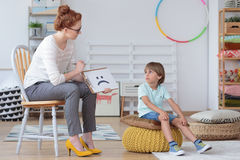 Boy sitting with counselor. Focused boy sitting on a yellow pouf, talking with a counselor sitting on chair in classroom stock photos