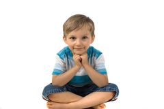 Boy sitting cross-legged. Cute little boy sitting on the cross legged on the floor and resting his chin on his arms.  Isolated on white background Royalty Free Stock Photography
