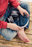 Boy sitting with crossed legs and holding headphones. New technology, home, leisure, and music concept Stock Photos