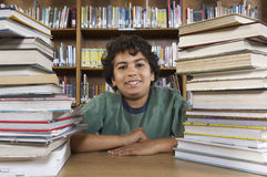 Boy Sitting At Desk With Books Royalty Free Stock Photo