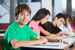 Boy Sitting At Desk With Friends Writing In Royalty Free Stock Photography