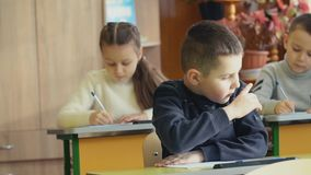 The boy is sitting at the desk. Boy sitting at his desk at school stock video footage