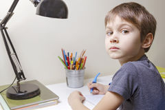 Boy sitting at the desk home and doing his homework. Child writting. School, children, education concept royalty free stock images