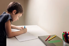Boy sitting at the desk home and doing his homework. Child writting. School, children, education concept. Boy writing at the desk at home. Child doing his Stock Image