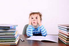 Boy sitting at a desk and looking up. Little boy with disheveled hair  sitting at a desk and looking up. boy 5 years. on the desk a lot of books. photo taken on Stock Photo