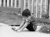 Boy Sitting Disappointed. A young boy (4 years) with face in arms, sitting on sidewalk beside fishing pole with sad and disappointed expression Royalty Free Stock Photo