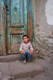 A boy sitting at the doorstep Stock Photos