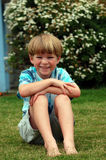 Boy sitting down in grass stock image