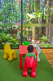 Boy sitting eco friendly living room nature. Vertical photo of a naturally balanced eco friendly living room with plants and trees both indoors and outdoors and Royalty Free Stock Photos