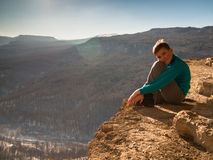 Boy sitting on the edge of the cliff. On the background of sky Stock Images