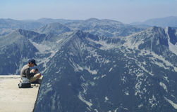 Boy sitting on the edge of a mountain lookout. Admiring the view of rugged alpine mountains with forested valleys with fine mist in a blue sky stock photography
