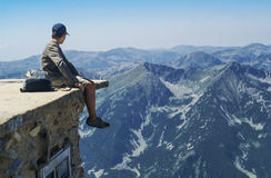 Boy sitting on the edge of a mountain lookout. Admiring the view of rugged alpine mountains with forested valleys with fine mist in a blue sky Stock Image
