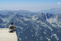 Boy sitting on the edge of a mountain lookout. Admiring the view of rugged alpine mountains with forested valleys with fine mist in a blue sky Stock Images