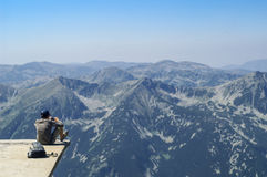 Boy sitting on the edge of a mountain lookout. Admiring the view of rugged alpine mountains with forested valleys with fine mist in a blue sky Royalty Free Stock Photography