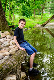 Boy Sitting at edge of stream Smiling royalty free stock photos