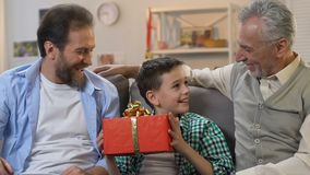 Boy sitting with eyes closed, father and grandpa giving birthday gift, surprise