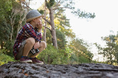 Boy sitting on the fallen tree trunk. In the forest Stock Photography