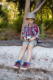Boy sitting on the fallen tree trunk in the forest. Portrait of boy sitting on the fallen tree trunk in the forest Stock Photography