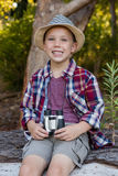 Boy sitting on the fallen tree trunk in the forest Stock Photos
