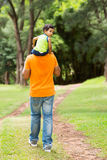 Boy sitting on father's shoulders Stock Images
