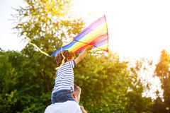 Boy sitting on father shoulders holding kite Royalty Free Stock Photos