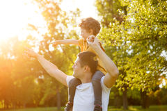 Boy sitting on father shoulders in park Stock Images