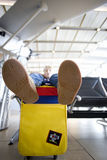 Boy (8-10) sitting with feet up on colourful bag in airport departure lounge, focus on soles of shoes in foreground Stock Photos