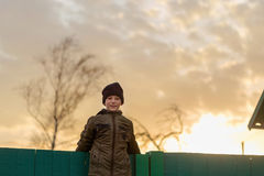 The boy is sitting on the fence at sunset Royalty Free Stock Image