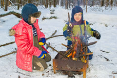 Boy sitting by the fire. Boy kindles bonfire in the winter forest Royalty Free Stock Image