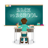 Boy is sitting on the first desk at the blackboard in primary sc Stock Image