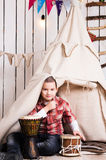 Boy sitting on the floor and playing drum near wigwam Royalty Free Stock Photo