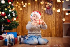 Boy and sitting on the floor with presents near christmas tree Royalty Free Stock Image