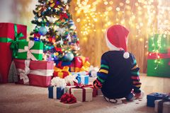Boy and sitting on the floor with presents near christmas tree Stock Photos