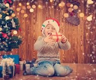 Boy and sitting on the floor with presents near christmas tree Royalty Free Stock Photography