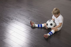 Boy Sitting On Floor With Soccer Ball Stock Photography