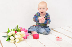 Boy sitting on floor of  white planks Stock Images