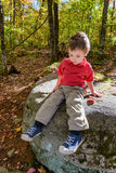 Boy Sitting in a Forest Lost in Thought. Lost in though, a young boy sits on a large rock in a forest during the fall season Royalty Free Stock Photo