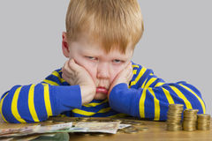 Boy sitting in front of a lot of money Royalty Free Stock Photography