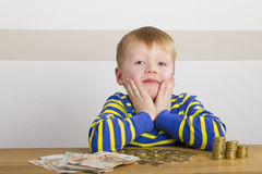 Boy sitting in front of money Stock Image