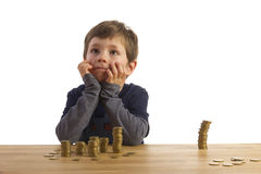 Boy sitting in front of money-towers Royalty Free Stock Photo